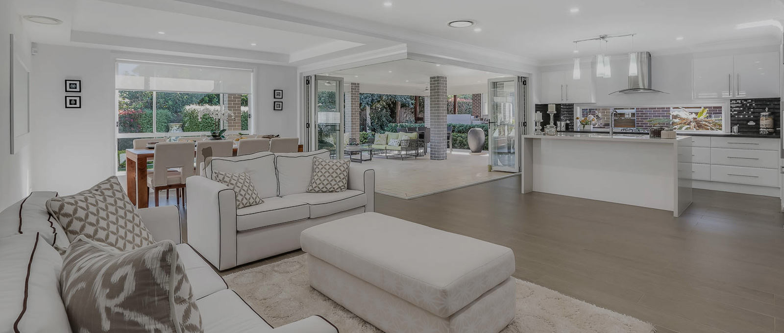 Interior of a modern house with a white sofa set and a dining area